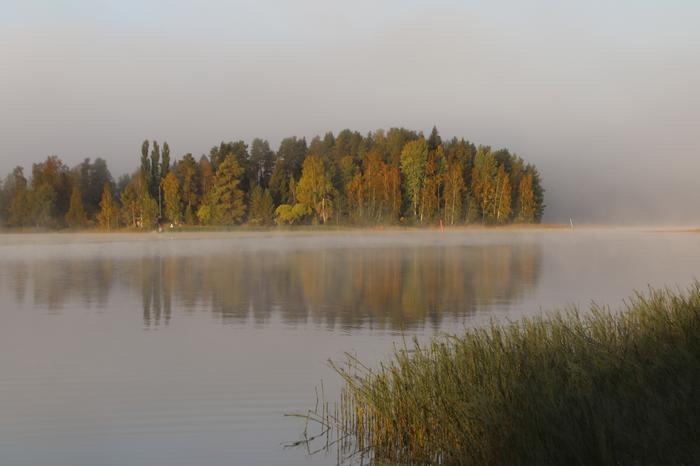 Sumupilvi peittää taivaan ja sumua on järven pinnassa.
