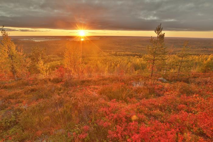 Aurinko laskee vaaran taa ja värjää maiseman punaisella.