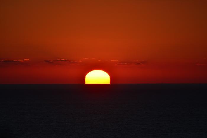 Auringonlasku kuvattuna meren takana.