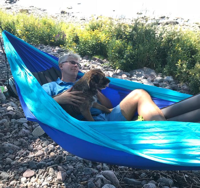 Forecan ja MTV Uutisten meteorologi Pekka Pouta ja Sini-koira nauttivat riippukeinussa pötköttelystä.