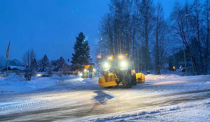 Aura-autoja työssään lumisateessa.