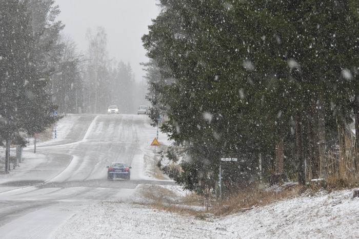 Liikennettä keväisessä lumisateessa.