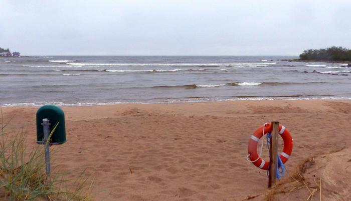 Sadetta, tuulta ja aaltoja autiolla uimarannalla.