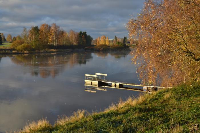 Syksyllä pilvien välistä pilkahtava aurinko valaisee puiden lehdet.