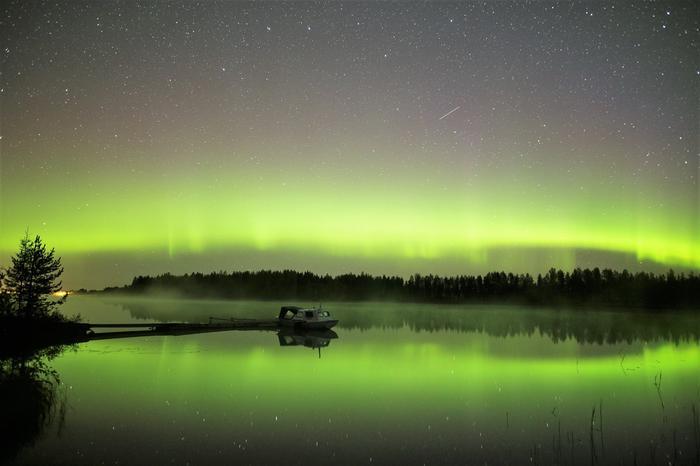 Aamuyön tunteina Oulujokeen heijastuvia revontulia.